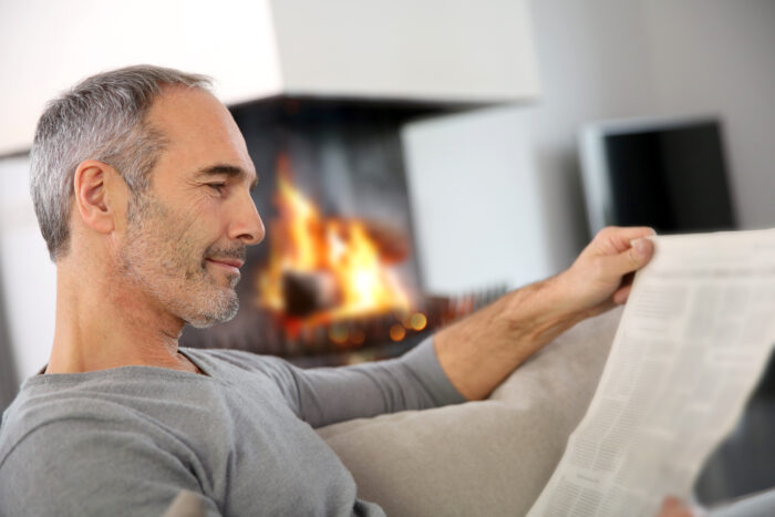 A retiree peacefully reading a newspaper by the fireplace