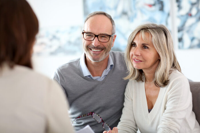 A senior couple discussing their retirement plan with a professional financial advisor